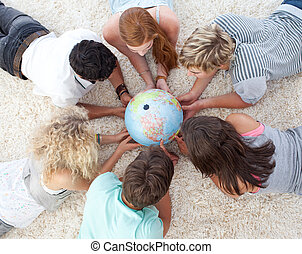 Group of teenagers lying on the floor examining a terrestrial world