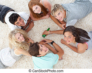 Group of teenagers playing spin the bottle - Group of ...