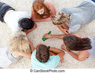 Group of teenagers playing with a bottle on the floor