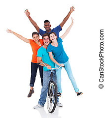 group of teenagers riding one bicycle