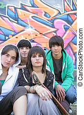 Group of teenagers sitting in front of a graffiti wall