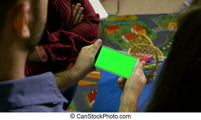 Group of teenagers watching a smart phone with green screen in a workshop