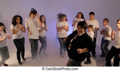 Group of teens dancing with a senior lady