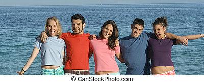 group of teens goofing on beach vaction in summer or spring break