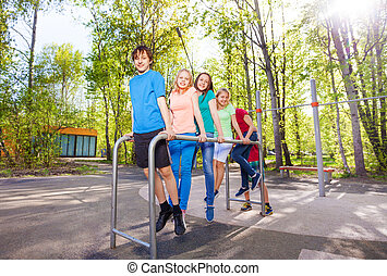 Group of teens holding and hanging on brachiating