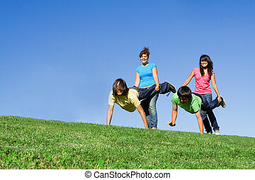 wheelbarrow race - group of teens playing wheelbarrow race...