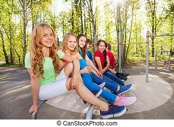 Group of teens sit on brachiating at playground