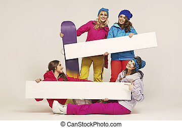 Group of the cheerful female snowboarders