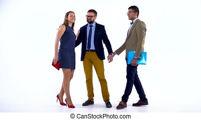 Group of three business partners posing in studio for camera. Slow motion
