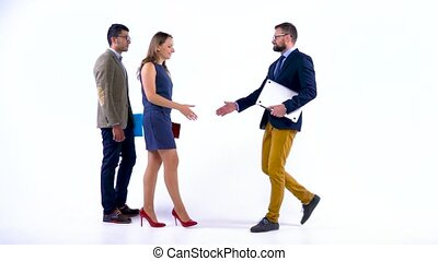 Group of three business partners shake hands welcoming each other in studio. Slow motion
