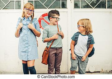 Group of three funny kids wearing backpacks walking back to school. Girl and boys wearing eyeglasses posing outdoors
