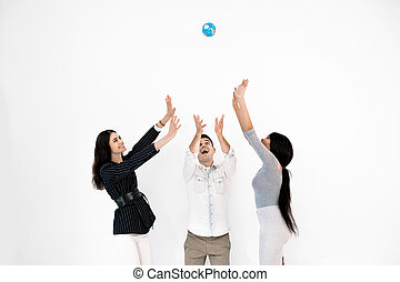 Group of three multiethnical international happy people throwing up little globe earth and looking up while it is levitating in the air. Education, travel, ecology concept