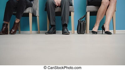 Group of three people sitting on chairs in queue line - ...