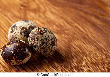 Group of three quail eggs on a wooden table, top view, close-up, selective focus, copy space.