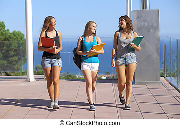 Group of three student teenagers walking towards camera