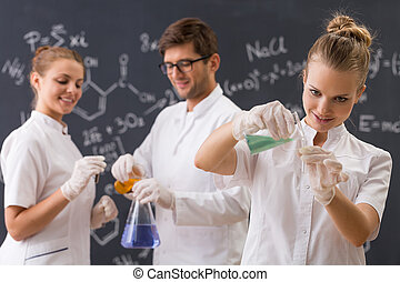 Group of three students conducting an experiment