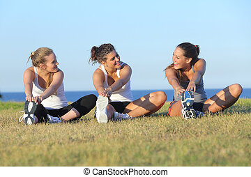 Group of three women stretching after sport on the grass ...