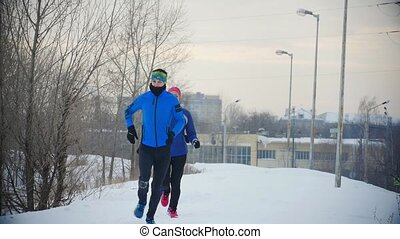 Group of three young athletes running technically in winter forest