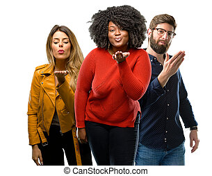 Group of three young men and women expressing love, blows kiss at camera, flirting