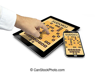 group of touchscreen devices with sudoku game and a finger touching