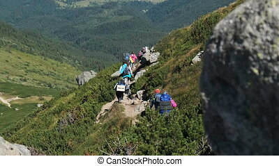 Group of Tourists and Children with Backpacks Go Down on Stone Trail in Mountain