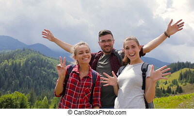 Group of tourists posing on camera in mountains in mountains
