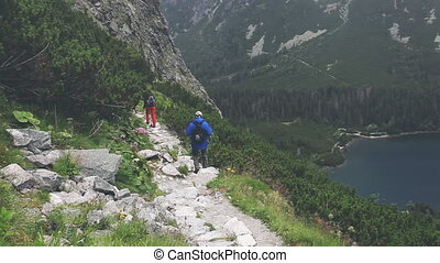 Group of tourists trekking in High Tatra mountains (Vysoke Tatry), Slovakia. People walking by stone trail over the precipice with mountain lake. Summer nature landscape. Camera turns right. Full HD
