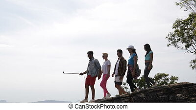 Group Of Tourists Walk On Mountain Top Holding Action Camera Happy Men And Women Over Beautiful Landscape Skyline In Morning