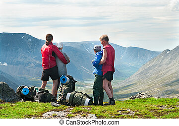 Group of travelers in mountains with knapsacks standing on mountain peak
