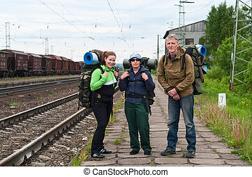 Group of travelers on railway station waiting a train. Mountaineering with knapsacks