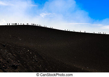Group of trekkers hiking on a volcano hill