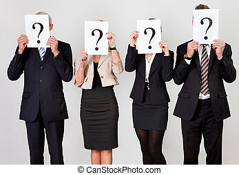 Group of unidentifiable business people hiding under question marks