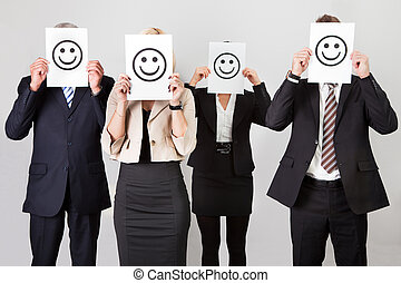 Group of unidentifiable business people hiding under smileys