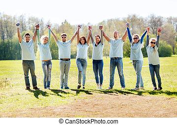 group of volunteers celebrating success in park -...