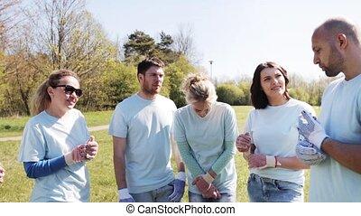 group of volunteers listening to mentor in park