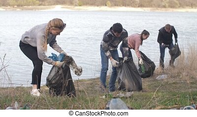 Group of volunteers picking up trash on the beach