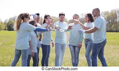 group of volunteers putting hands on top in park