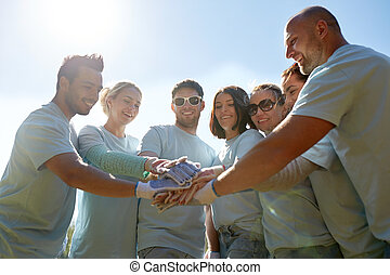 group of volunteers putting hands on top outdoors -...