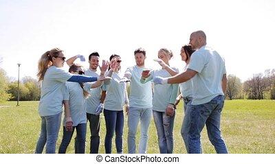 group of volunteers putting hands on top in park -...
