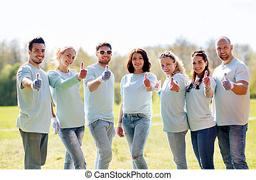 group of volunteers showing thumbs up in park