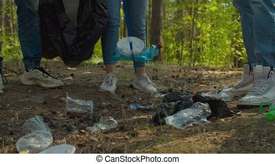 Low section of diverse young volunteers tidying up rubbish in forest using garden tools. Group of charity eco activists picking up plastic waste and garbage in woodland. Environmental awareness.
