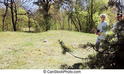 group of volunteers with tree seedlings in park -...
