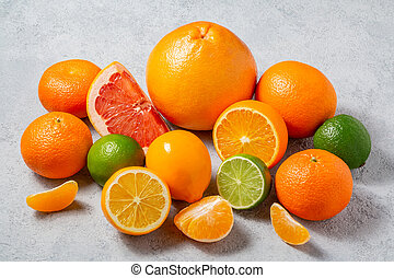 group of whole and sliced citrus fruits - tangerines, lemons, limes, oranges, grapefruits on the surface of the gray table - image