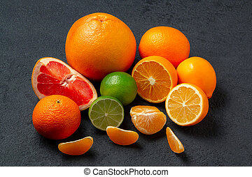 group of whole and sliced citrus fruits - tangerines, lemons, limes, oranges, grapefruits on the surface of the dark table