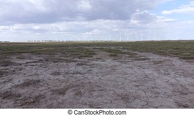 Group of wind turbines in the background of parched land...