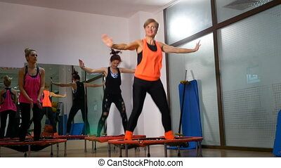Group of women at the fitness club doing aerobics with mini trampoline