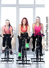 Group of women cycling in gym