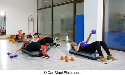 Group of women doing exercises with leg raises at the fitness club