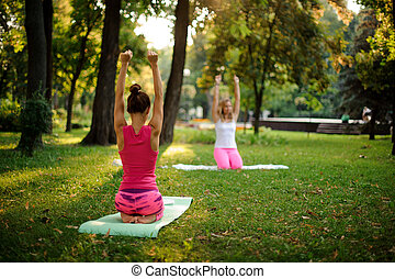 Group of women doing yoga exercises on green grass in the park