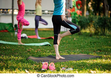 Group of women doing yoga exercises on the grass in a park. Legs shot